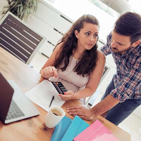 Uma mulher e um homem sentado à frente de um notebook conversando