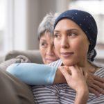 Mulher olhando para o lado com lenço na cabeça como uma pessoa que luta contra o câncers, endo abraçada por sua mãe.