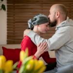 Homem dando beijo na cabeça da mulher com lenço, como alguém que passou por quilioterapia