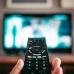 Imagem de um controle com uma TV ao fundo